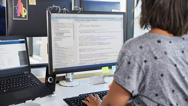 A woman sitting at her desk in front of a monitor coding.